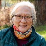 Photo of Inez Fung outdoors with trees and grass in background; she is smiling, wearing glasses, a patterned scarf and weatherproof jacket