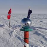 South Pole photo by UCB Climate Scientist Professor Inez Fung.   The ice at the South Pole is moving at the rate of 10 meters per year.  So there is a row of flags marking the previous positions of the ceremonial marker.