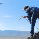 student stands on tall, sheer rock outcrop taking measurements for field geology class